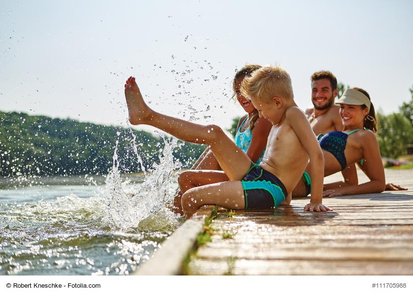 Familie und Kinder plantschen im Wasser