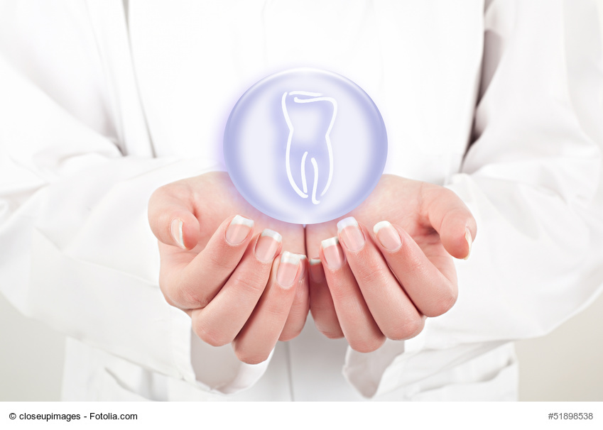 doctor woman holding teeth symbol in her hands