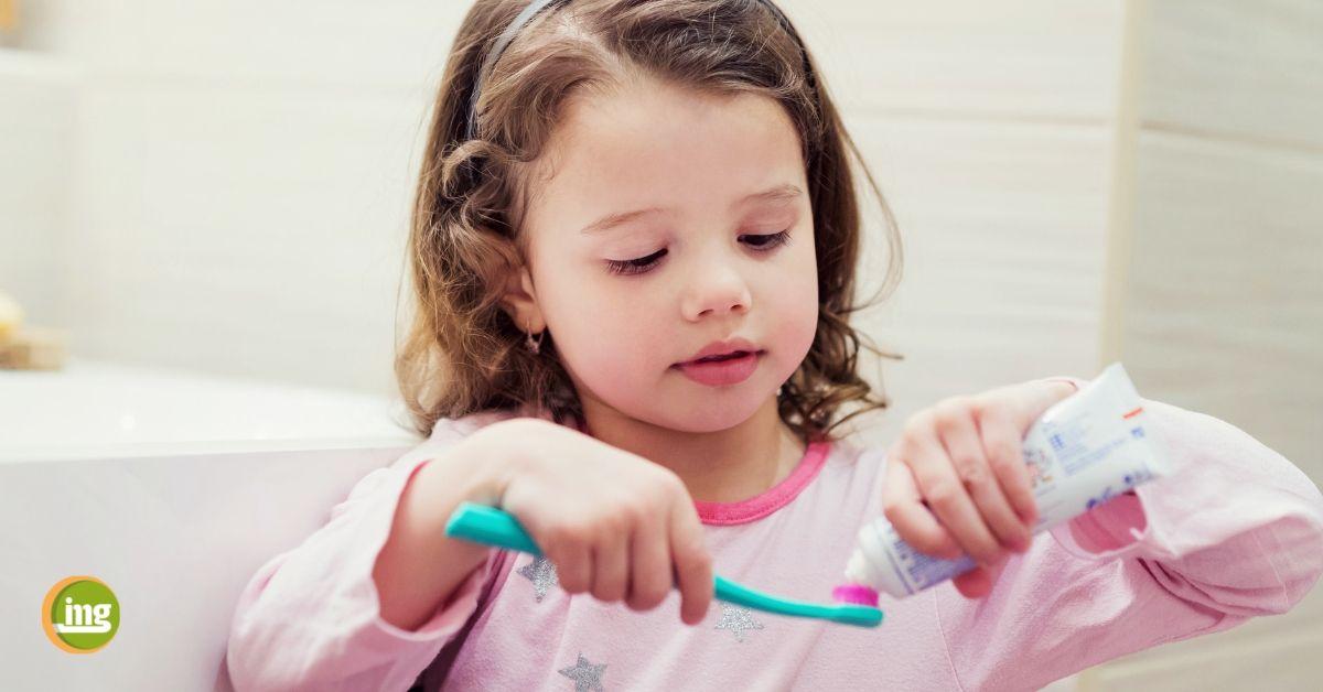 Kleines Mädchen mit Zahnbürste und Zahnpasta. Information Mundgesundheit klärt zu Fluoriden auf.