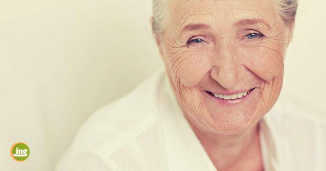 Seniorin freut sich, dass sie beim Setzen von Zahnimplantaten keine Schmerzen hatte.