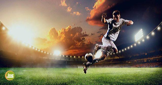 Ein Fußballer tritt gegen den Ball und Information Mundgesundheit erklärt, was die Zähne mit Sport zu tun haben.