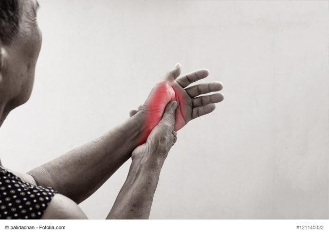 Ältere Dame mit Schmerzen massiert ihr Handgelenk