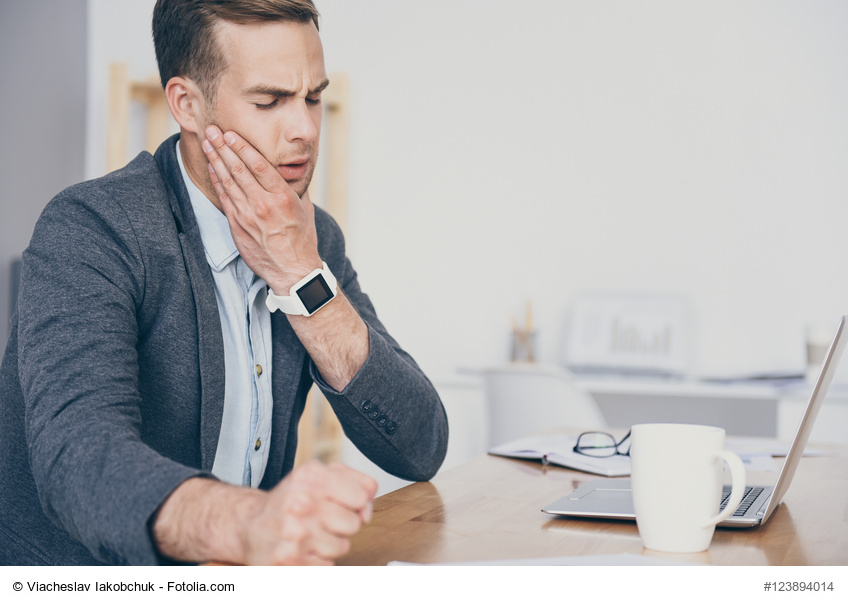 Junger Mann mit Zahnschmerzen und einer Tasse Tee sitzt vor demComputer