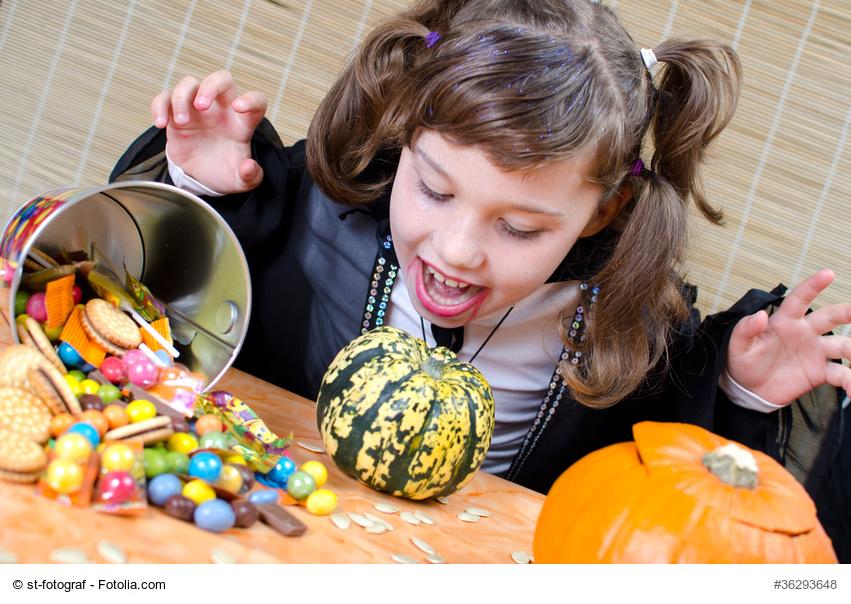 kleines vampirmädchen mit süßigkeiten zu halloween