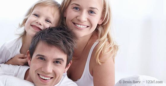 Junge Familie lacht in die Kamera