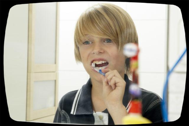junge steht vor dem spiegel und putzt sich die zähne