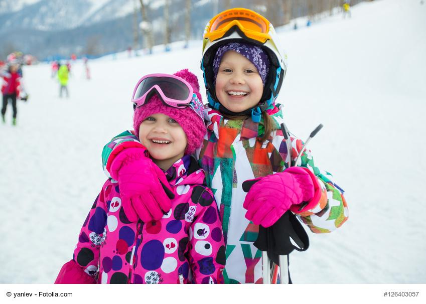 kinder im schnee, lachen und zeigen ihre zähne beim skifahren