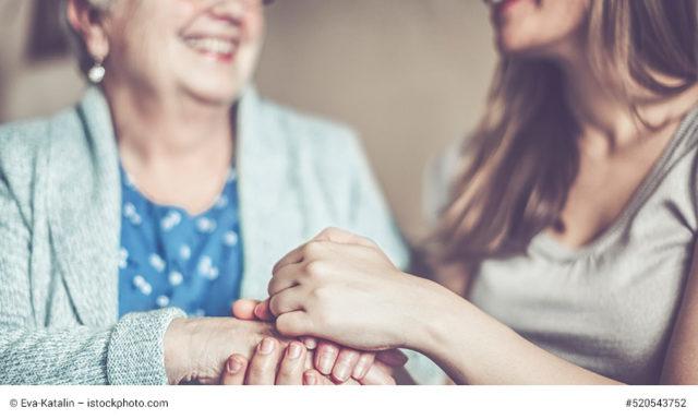 junge frau hält seniorin die hand zum internationalen Tag der Pflege