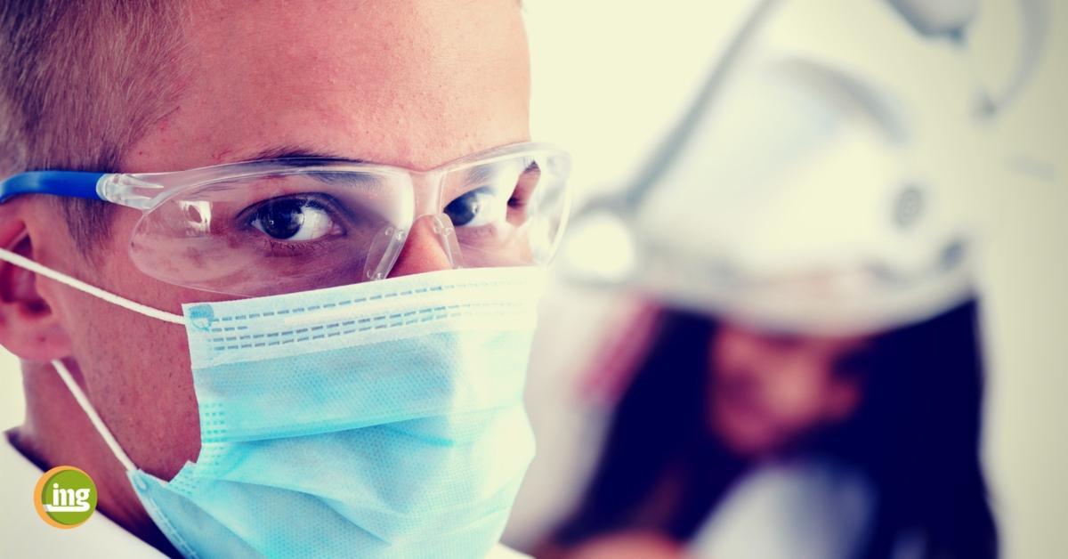 zahnarzt mit munschutz schaut in die kamera - frau im hintergrund behandelt