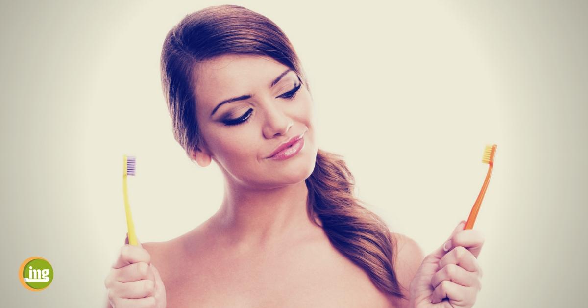 attraktive frau hält zwei zahnbürsten in der hand