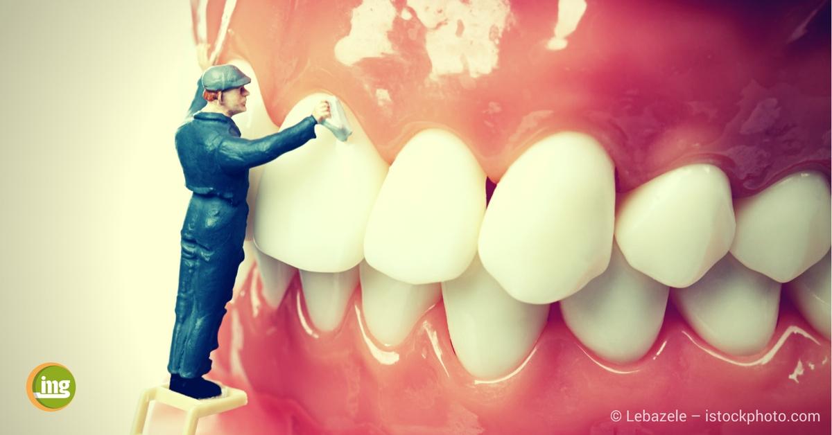 Mann auf Leiter putzt riesengroße Zahnprothese