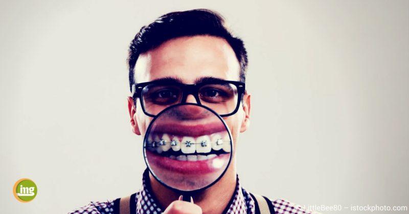 mann mit zahnspange und lupe vor dem mund