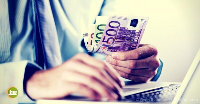 ein mann zählt geld für dem computer und fragt sich: was kosten eigentlich zahnimplantate? information mundgesundheit gibt die antwort