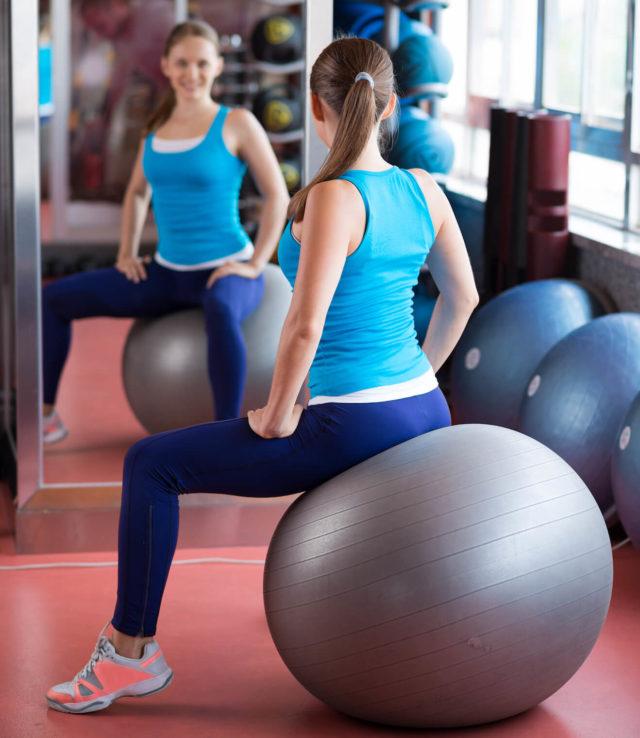 Frau sitzt auf Pilates-Ball: Zum Tag der Tag der Rückengesundheit am 15. März erklärt Information Mundgesundheit, wie Zähne, Kiefer und Wirbelsäule zusammenhängen.