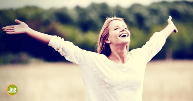 Junge Frau breitet die Arme aus und lacht. Information Mundgesundheit informiert zum Lass-uns-lachen-Tag. Warum ist Lachen so gesund für uns?