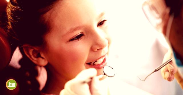 Zahnärztin untersucht Mädchen auf die Molaren-Inzisiven-Hypomineralisation (MIH). Ihre Zähne sind viel empfindlicher und anfälliger für Erkrankungen wie Karies. Information Mundgesundheit erklärt, wie MIH entsteht und was der Zahnarzt tun kann.