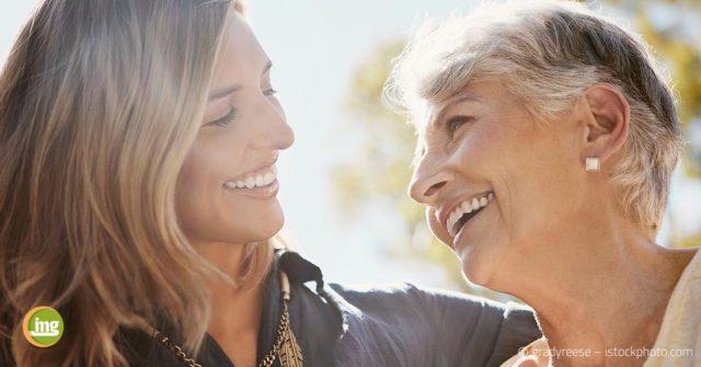 Junge Frau und alte Frau lächeln sich an