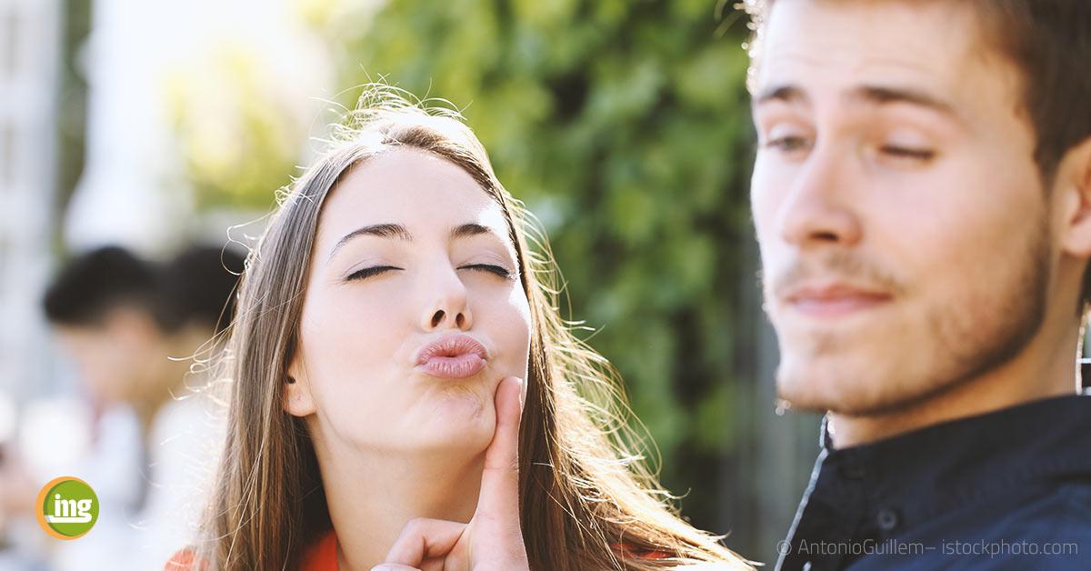 Junge Frau möchte jungen Mann küssen und wird abgewiesen. Information Mundgesundheit und Gründe, warum Menschen nicht mehr geküsst werden.
