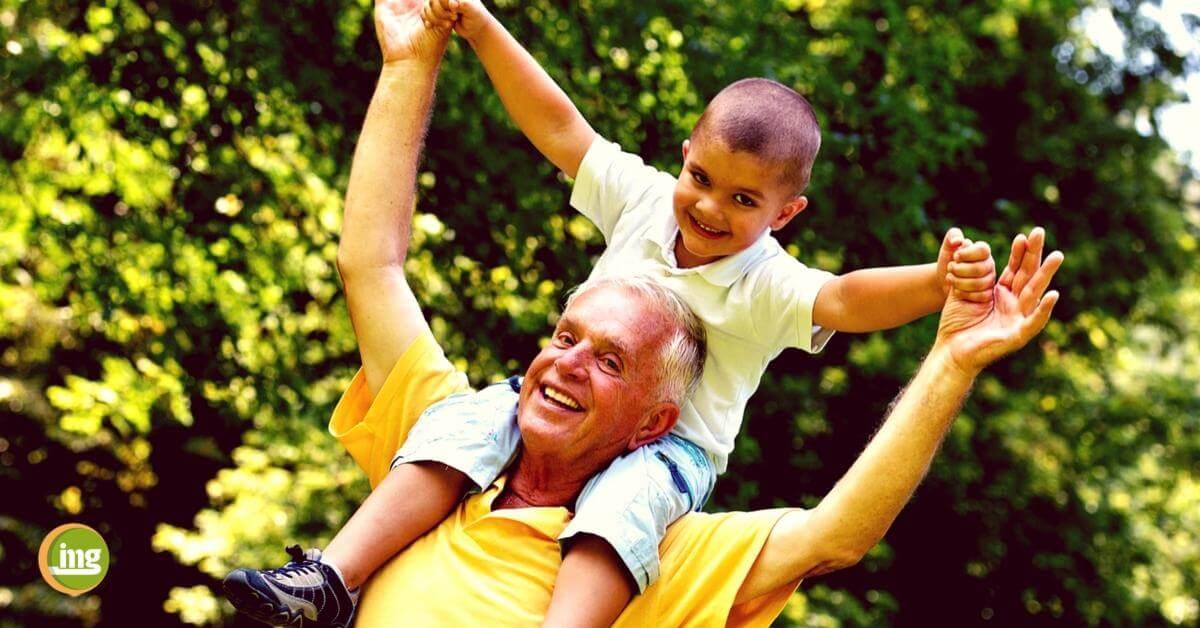 Großvater trägt Kind auf den Schultern und beide lachen. Zum Weltgesundheitstag 2018 geht es um den Einfluss der Mundgesundheit (Parodontitis / Parodontose / Karies) auf den Körper und auf unsere allgemeine Gesundheit!