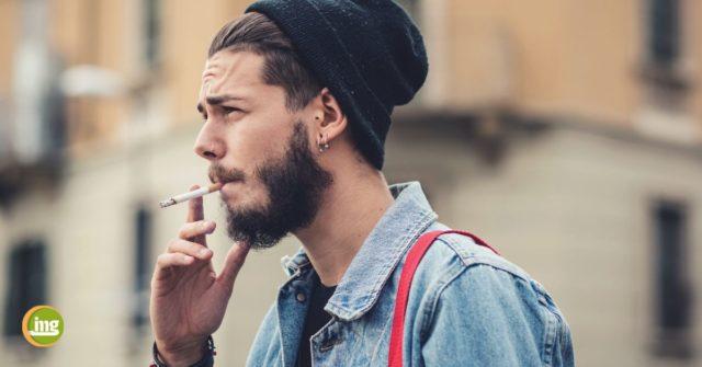 Junger Mann raucht eine Zigarette, weil er sich nicht über die Folgen für die Zahngesundheit aufgeklärt hat.