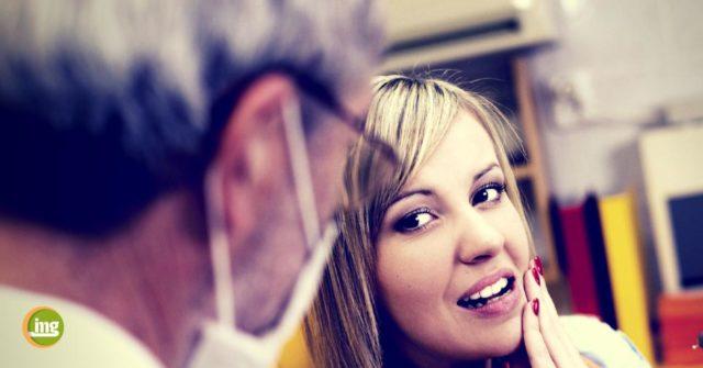 Frau auf dem Zahnarztstuhl hält sich die Wange und erklärt dem Zahnarzt ihre Angst