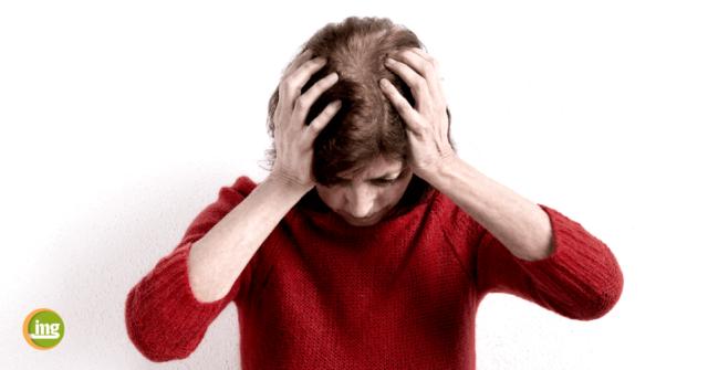 Frau in rotem Pullover hält sich den Kopf. Information Mundgesundheit berichtet zum Tag gegen den Schlaganfall über Parodontitis als Risikofaktor für Gehirn und Herz.