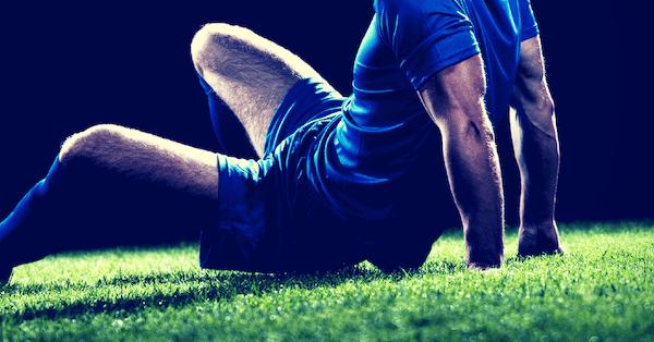 Fußballer sitzt auf dem grünen Rasen