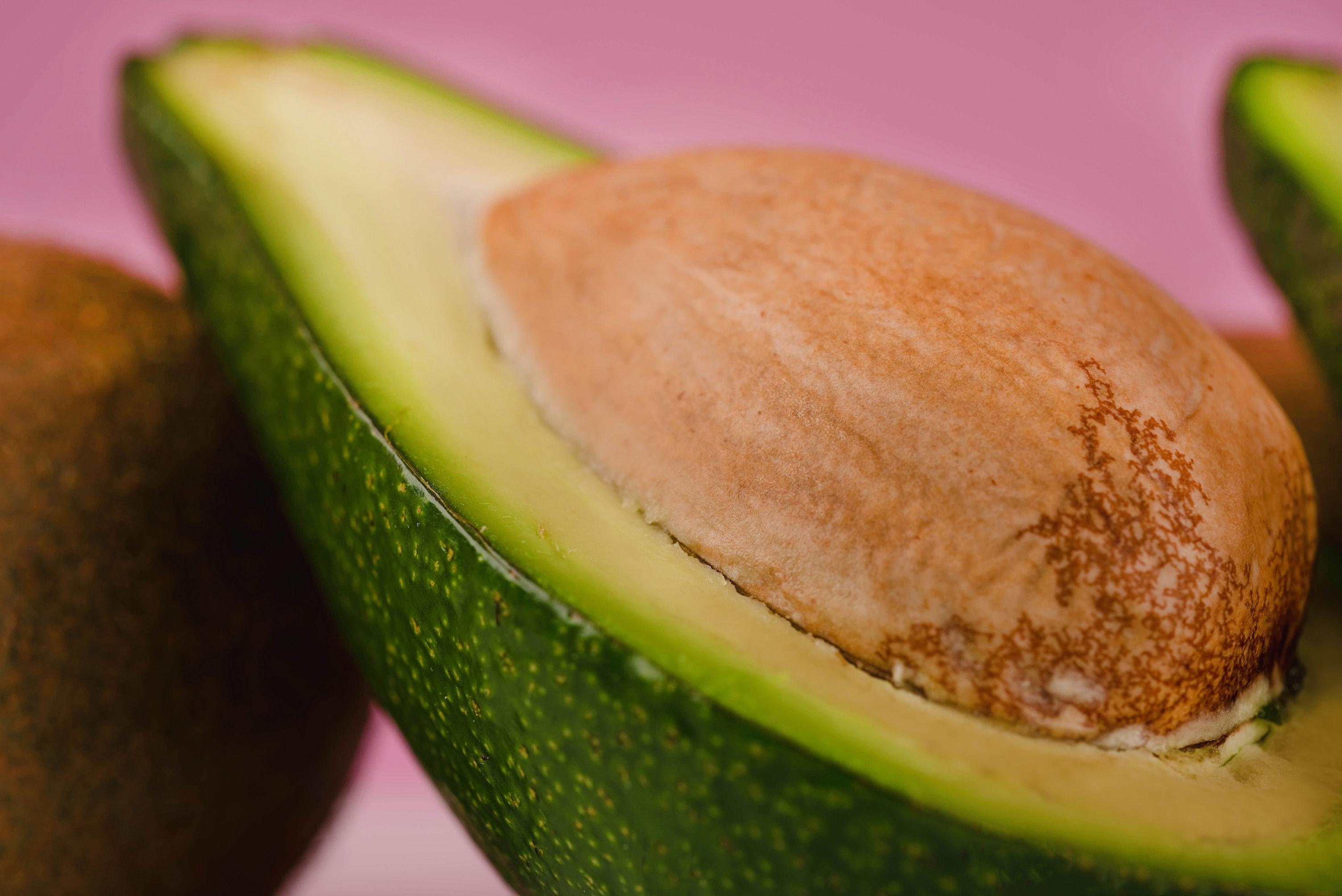 Im bild ist eine aufgeschnittene Avocado mit Kern groß zu sehen.