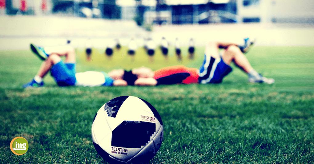 Fußballer liegen auf dem Rasen und Information Mundgesundheit erklärt, warum die DFB-11 in Russland geusnde Zähne für gesunden Schlaf und eine optimale Leistung braucht.