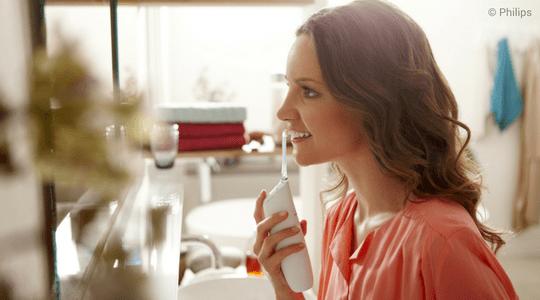Junge Frau reinigt die Zahnzwischenräume mit der elektrischen Munddusche Philips Airfloss