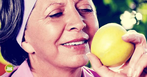 Ältere Dame schaut Apfel an, um ihn mit festen Zähnen und Zahnimplantaten zu essen.