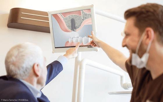Implantologie erklärt älterem Patienten die Versorgung mit einem Zahnimplantat.