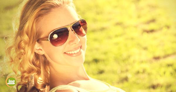 Junge Frau mit Sonnenbrille genießt den Sommer. Aber welche Folgen hat die Hitze für die Zähne und die Mundgesundheit?
