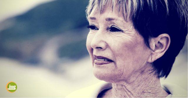 Ältere Frau schaut am Strand n die Ferne. Hier lesen Sie bei Information Mundesundheit, wie fehlende Zähne das Aussehen beeinflussen.