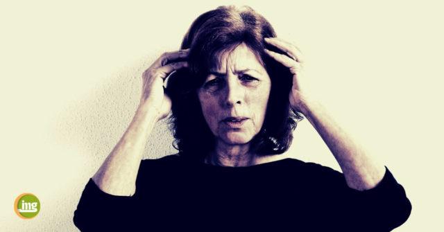 Ältere Frau mit Kopfschmerzen, hält sich die Schläfen. Informationen zum Weltschlaganfall-Tag 2018 von Information Mundgesundheit.