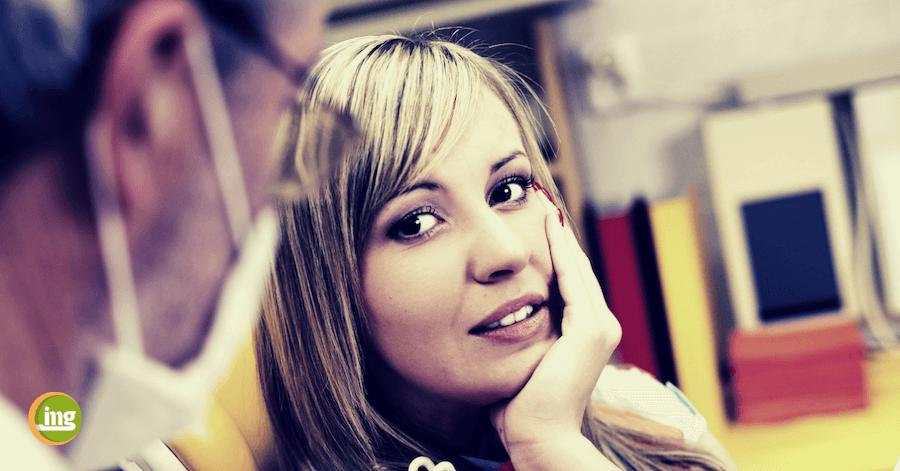 Frau mit Zahnschmerzen in der Zahnarztpraxis. Information Mundgesundheit erklärt, warum Zahnschmerzen nicht angekündigt werden sollten.