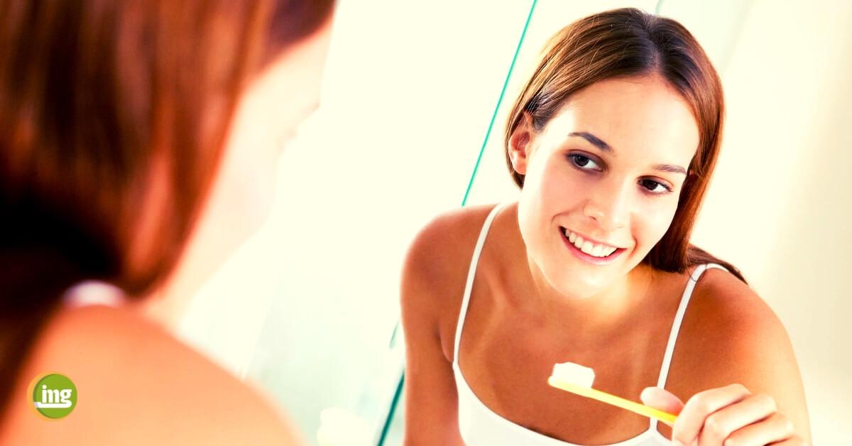 Frau mit Zahnbürste vor dem Spiegel. Studie zeigt: erst Zahnseide, dann Zähne putzen. Bericht auf Information Mundgesundheit