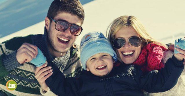 Junge Familie mit Kind im Schnee. Information Mundgesundheit berichtet über Zähne, Kälte und wie man sich vor Zahnschmerzen schützen kann.