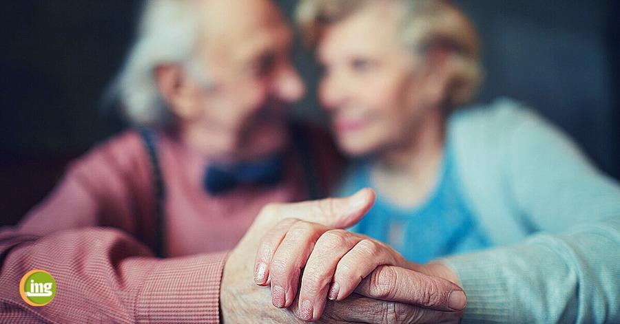 Älters Paar gibt sich die Hand und Information Mundgesundheit erklärt: Was ist ein Seniorenzahnarzt?