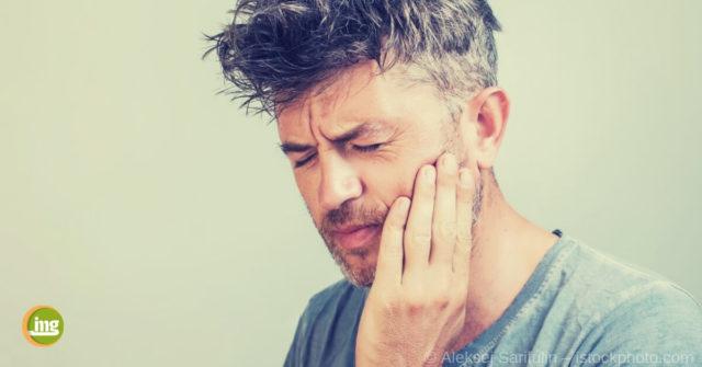 Mann hält sich die Backe vor Zahnschmerzen, kennt aber nicht die Ursachen. Information Mundgeseundheit klärt auf zum Tag der Zahnschmerzen