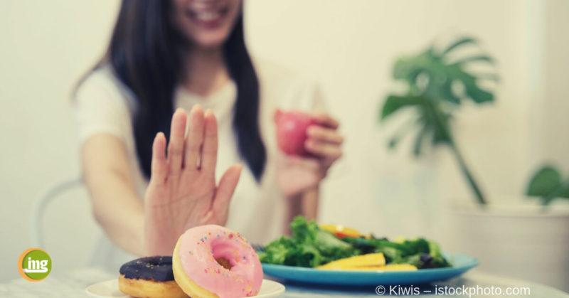 Frau schiebt Donuts weg, weil sie sich jetzt zur Fastenzeit zuckerfrei ernähren möchte.