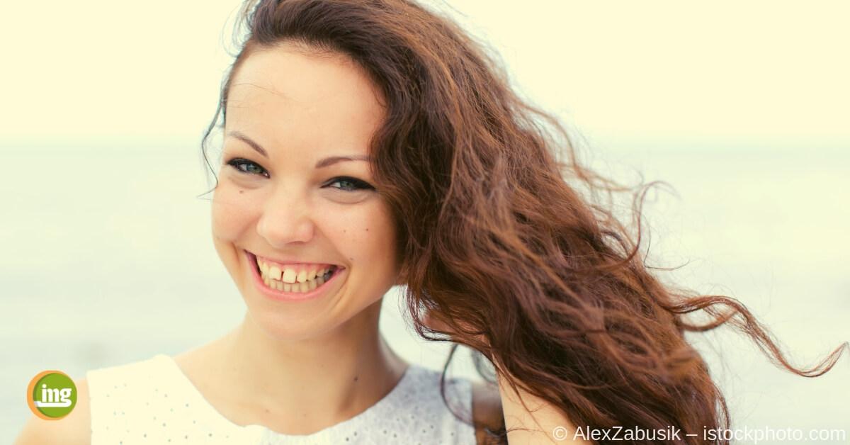 Junge Frau lächelt mit Zahnlücke zwischen den vorderen Schneidezähnen.