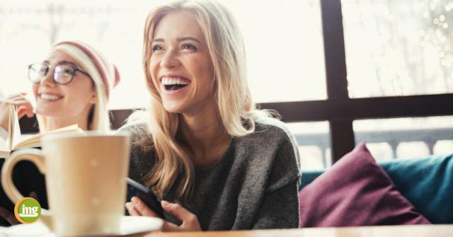 Eine junge Frau lacht mit schönen Zähnen dank Veneers am Weltlachtag 2019.