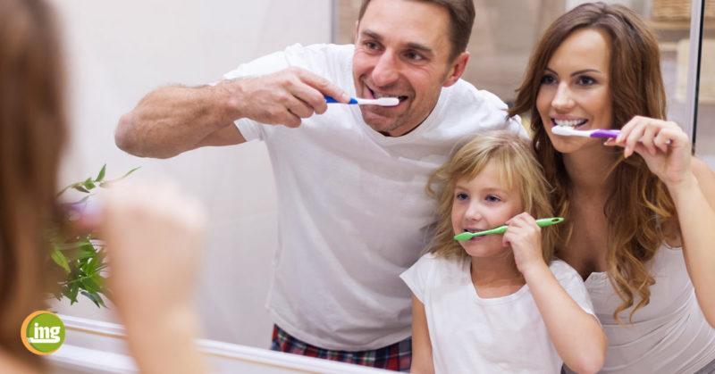 Vater und Sohn putzen sich im Badezimmer die Zähne. Information Mundgesundheit klärt auf: So helfen Eltern als gute Vorbilder..