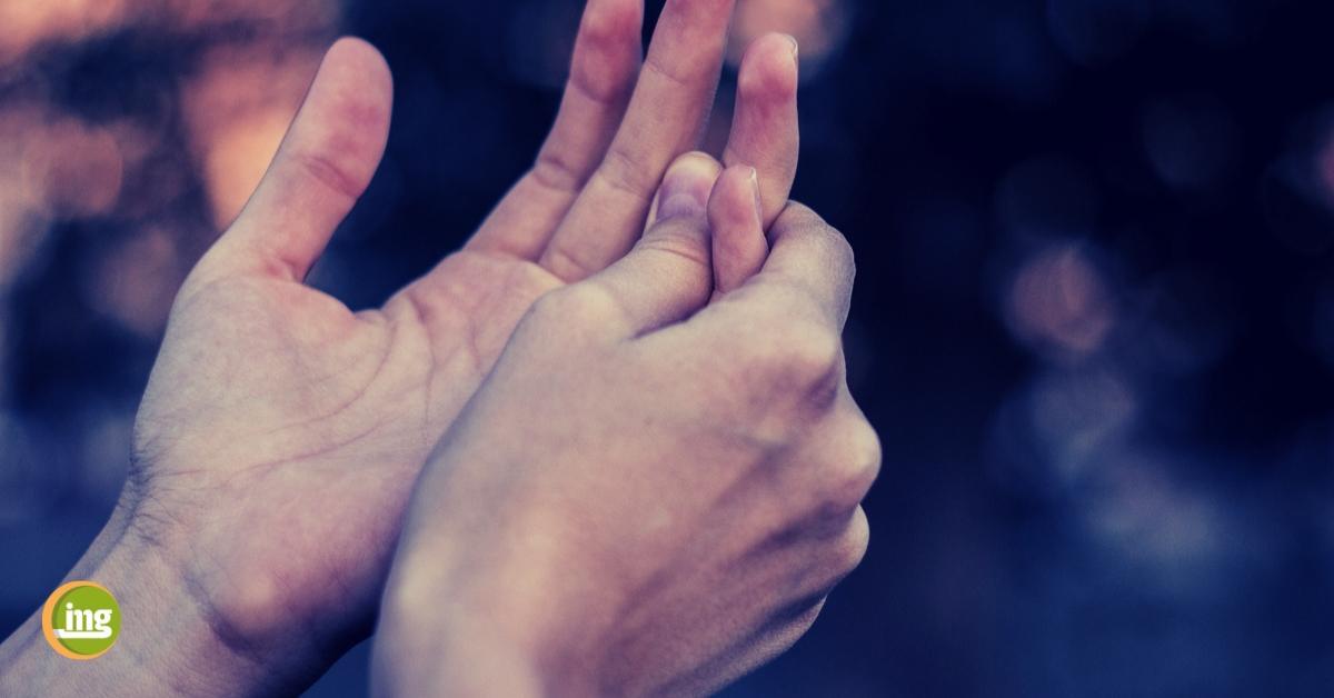 Patient reibt sich die Finger. INformation Mundgesundheit berichtet zum Welt-Rheumatag.