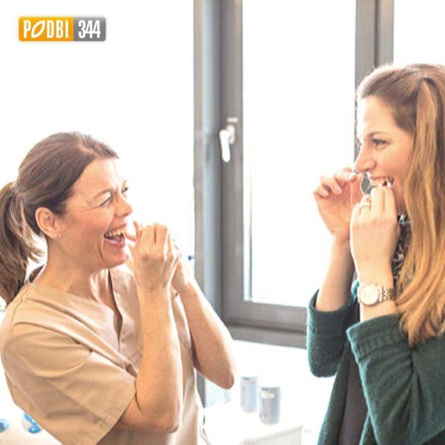 In der Zahnarztpraxis PODBI344 in Hannover erklärt die Prophylaxe-Assistentin wie mit Zahnseide gereinigt wird