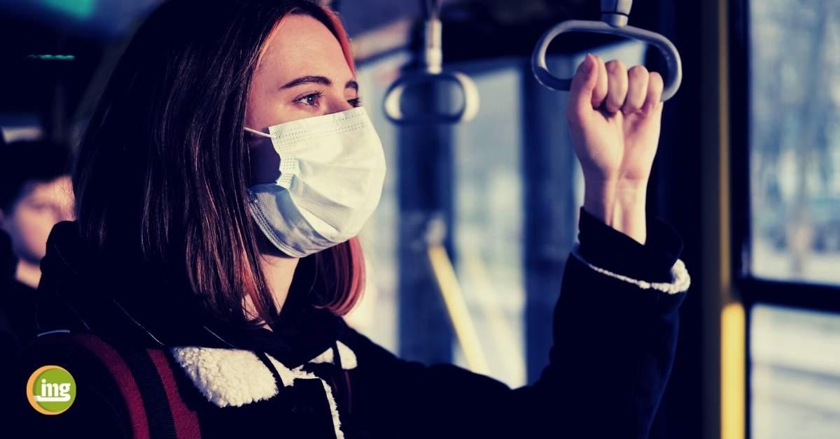 Frau mit Maske in der Straßenbahn. Artikel zu Corona in der Zahnarztpraxis von Information Mundgesundheit.