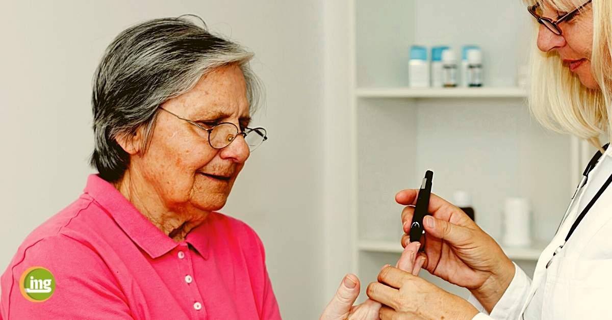 Ältere Patientin bei Ärztin zur Blutzuckermessung. Information Mundgesundheit berichtet über Corona, Diabetes und Parodontitis zum Weltdiabetestag 2020.