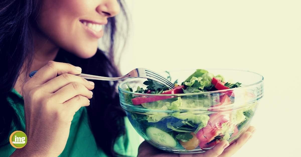 Eine junge Frau isst einen Salat. Information Mundgesundheit klärt zu gesunder Ernährung im Corona-Winter auf und fragt, was wir für ein starkes Immunsystem tun können.